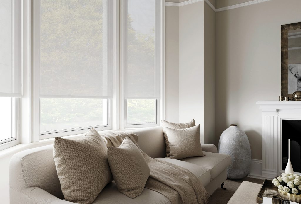 An image showing white sheer roller blinds in a light and spacious living room