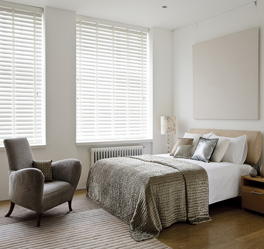 White wooden blinds in a bedroom